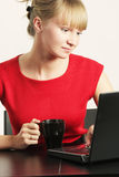 Blonde Geschäftsfrau in der roten Funktion auf Laptop Lizenzfreie Stockbilder