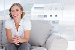 Blonde Geschäftsfrau, die auf Couch sitzt Stockfotos