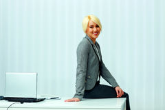 Blonde Geschäftsfrau, die auf dem Tisch sitzt Stockfotos