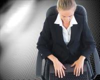 Blonde Geschäftsfrau, die auf Drehstuhl mit Laptop sitzt Lizenzfreie Stockbilder