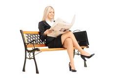 Blonde Geschäftsfrau, die auf einer Bank sitzt und Zeitung liest Stockbilder