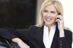 Blonde Geschäftsfrau, die auf ihrem Handy spricht Lizenzfreie Stockfotos