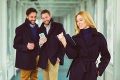Blonde Geschäftsfrau, die auf Tablette in der Lobby mit Kollegen Hintergrund betrachtet Stockfoto