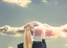 Blonde Geschäftsfrau, die auf Wolke zeigt Stockbild