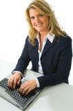 Blonde Geschäftsfrau, die an Computer arbeitet Stockfotografie