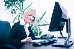 Blonde Geschäftsfrau, die an Computer im Büro arbeitet Stockfotos