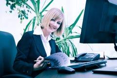Blonde Geschäftsfrau, die an Computer im Büro arbeitet Stockbild
