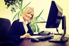 Blonde Geschäftsfrau, die an Computer im Büro arbeitet Lizenzfreie Stockfotografie