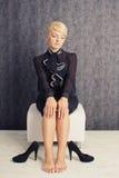 Blonde Geschäftsfrau, die in der Klage mit Schuhen sitzt Stockbild
