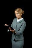 Blonde Geschäftsfrau, die digitale Tablette auf Schwarzem verwendet Stockbild