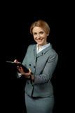 Blonde Geschäftsfrau, die digitale Tablette verwendet und an der Kamera lächelt Stockbilder