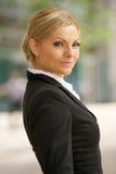 Blonde Geschäftsfrau, die draußen steht Stockbild