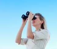 Blonde Geschäftsfrau, die durch Binokel schaut Stockbilder
