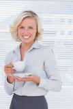 Blonde Geschäftsfrau, die eine Schale hält Stockfoto