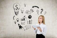 Blonde Geschäftsfrau, die eine Tablette nahe einer Geschäftsideenskizze hält Lizenzfreie Stockbilder