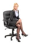 Blonde Geschäftsfrau, die in einem Bürostuhl sitzt Stockbilder