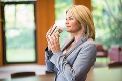 Blonde Geschäftsfrau, die einen Kaffee trinkt Stockbild