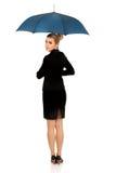 Blonde Geschäftsfrau, die einen Regenschirm hält Lizenzfreies Stockbild