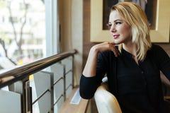 Blonde Geschäftsfrau, die heraus das Fenster schaut Stockfoto