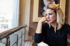 Blonde Geschäftsfrau, die heraus das Fenster schaut Lizenzfreies Stockfoto