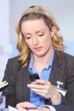 Blonde Geschäftsfrau, die ihren Handy verwendet Stockbilder