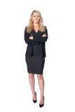Blonde Geschäftsfrau, die im dunklen Anzug, lokalisiert auf Weiß steht Lizenzfreies Stockfoto