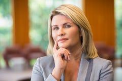 Blonde Geschäftsfrau, die Kamera betrachtend denkt Stockbild