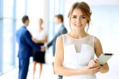 Blonde Geschäftsfrau, die Kamera betrachtet Stockfotos