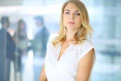 Blonde Geschäftsfrau, die Kamera betrachtet Lizenzfreie Stockfotos