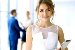 Blonde Geschäftsfrau, die Kamera betrachtet Stockbilder