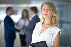 Blonde Geschäftsfrau, die Kamera betrachtet Stockfotografie