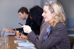 Blonde Geschäftsfrau, die am Konferenztische sitzt Stockfotos