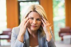 Blonde Geschäftsfrau, die Kopfschmerzen erhält Lizenzfreie Stockbilder