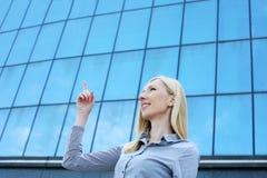 Blonde Geschäftsfrau, die mit dem Finger oben darstellt Stockfoto