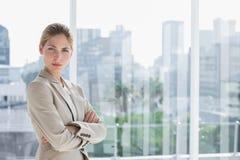 Blonde Geschäftsfrau, die mit den Armen gekreuzt steht Stockfotos