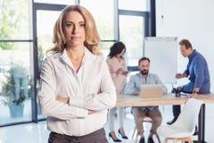 Blonde Geschäftsfrau, die mit den gekreuzten Armen steht und Kamera betrachtet Lizenzfreie Stockfotos