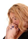 Blonde Geschäftsfrau, die mit geschlossenem Auge betet Lizenzfreies Stockfoto