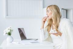 blonde Geschäftsfrau, die mit Laptop arbeitet und weiße Süßigkeiten im modernen Licht isst Stockfotografie