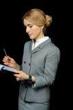 Blonde Geschäftsfrau, die Ordner mit Papieren und Stift auf Schwarzem hält Stockfotografie
