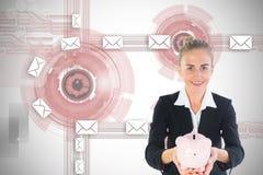 Blonde Geschäftsfrau, die rosa Sparschwein hält Stockfotografie