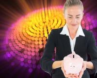 Blonde Geschäftsfrau, die Sparschwein hält Lizenzfreie Stockfotografie