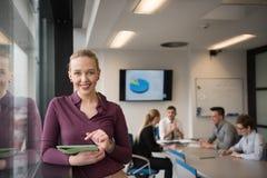 Blonde Geschäftsfrau, die an Tablette im Büro arbeitet Lizenzfreies Stockbild