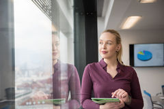Blonde Geschäftsfrau, die an Tablette im Büro arbeitet Lizenzfreie Stockfotos