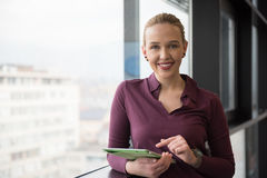 Blonde Geschäftsfrau, die an Tablette im Büro arbeitet Stockbild