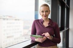 Blonde Geschäftsfrau, die an Tablette im Büro arbeitet Stockfotos