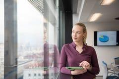 Blonde Geschäftsfrau, die an Tablette im Büro arbeitet Stockfotografie