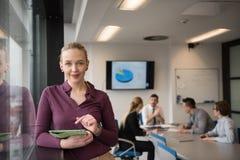 Blonde Geschäftsfrau, die an Tablette im Büro arbeitet Lizenzfreies Stockfoto