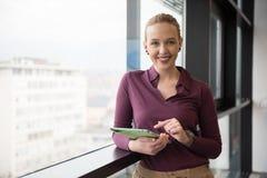 Blonde Geschäftsfrau, die an Tablette im Büro arbeitet Lizenzfreie Stockfotografie