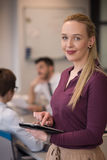 Blonde Geschäftsfrau, die an Tablette im Büro arbeitet Stockbilder