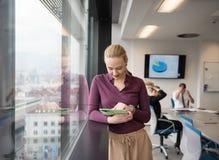 Blonde Geschäftsfrau, die an Tablette im Büro arbeitet Lizenzfreie Stockbilder